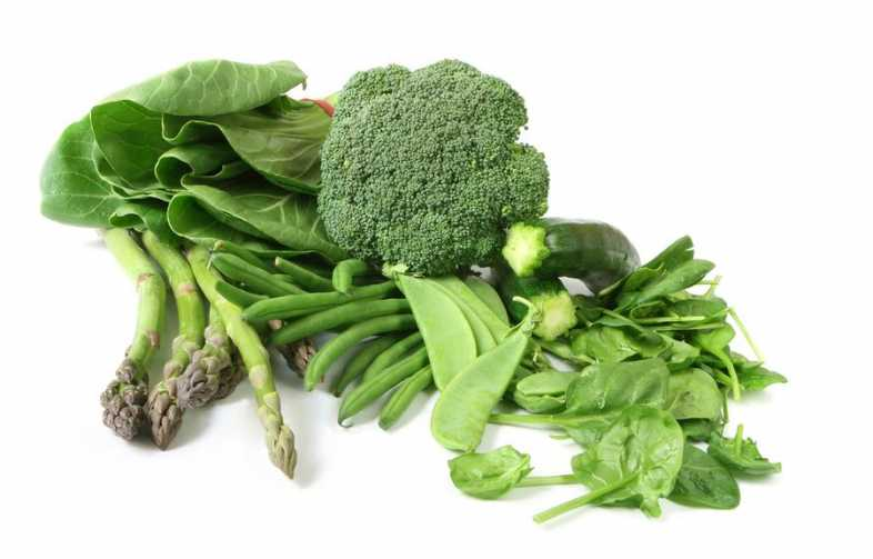 Green vegetables on white background. Includes asparagus zucchini or courgette broccoli bok choy beans spinach and snow peas.