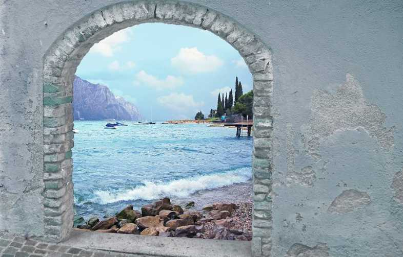view through rustic vintage door to mountain lake and mediterranean landscape